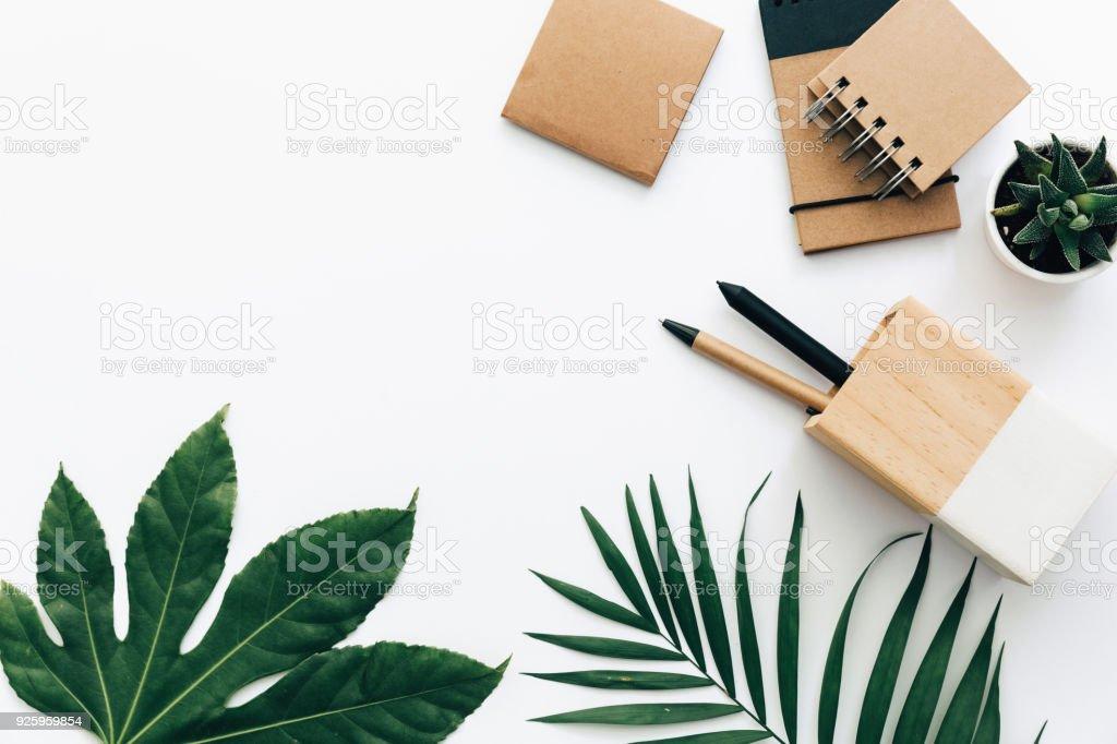 Folhas de mínima tabela de mesa de escritório com papelaria, suprimentos e palm. Vista superior com espaço de cópia, plano criativo de leigos. - foto de acervo