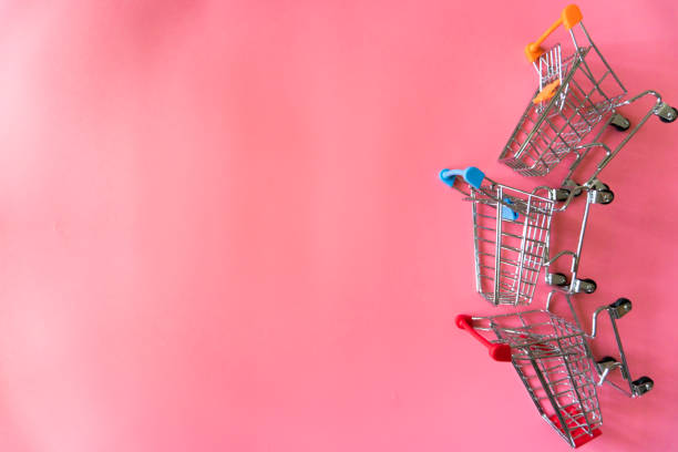Minimal shopping online concept, Colorful paper shopping bag and trolley go down from floating pink background for copy space. Customer can buy everthing form home and the messenger will deliver. Minimal shopping online concept, Colorful paper shopping bag and trolley go down from floating pink background for copy space. Customer can buy everything form home and the messenger will deliver. discount store stock pictures, royalty-free photos & images
