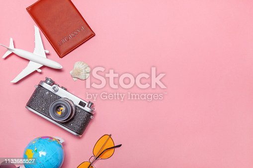 Vacation travel summer weekend sea adventure trip concept. Minimal simple flat lay with plane vintage camera passport sunglasses globe piggy bank and shell on pink pastel trendy modern background