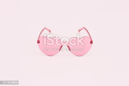 Minimal style fashion photography with heart shaped glasses on pink background. Pink modern sunglasses.  Trendly summer concept. Copy space.