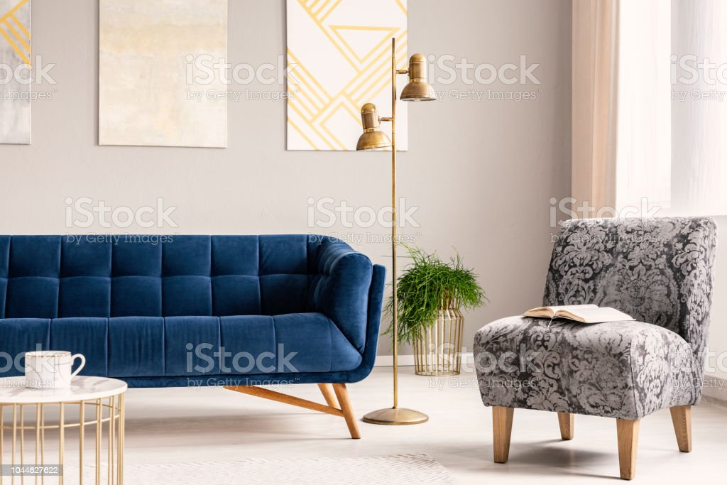 Picture of: Minimal Style Living Room Interior With A Navy Blue Couch A Patterned Gray Armchair And Gold Accents Of A Lamp A Coffee Table And A Flower Stand Real Photo Stock Photo