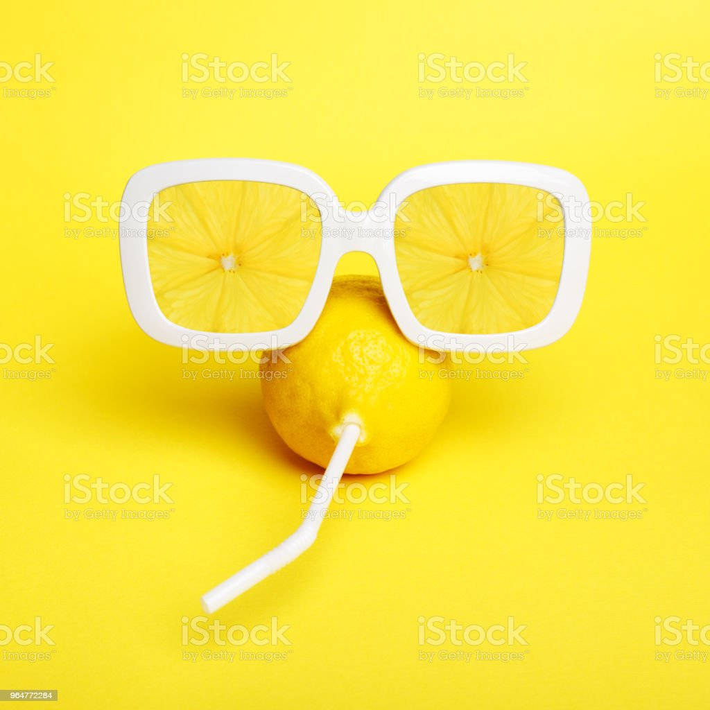 Minimal tropic lemon in vintage sunglasses with straw on yellow. royalty-free stock photo