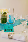 Minimal wedding arrangement for the bride's table in turquoise blue and white featuring a white roses bouquet, cotton napkins with silver rings, tag with fine calligraphy and a decorative centerpiece.