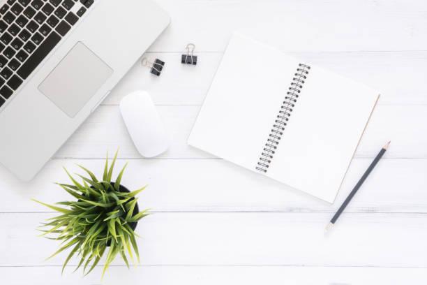 Minimale Arbeitsraum - kreative Wohnung lag Foto des Arbeitsbereichs Schreibtisch. Ansicht Büroschreibtisch mit Laptop, mock auffüllen Notizbücher und Pflanze auf weißem Hintergrund aus Holz. Draufsicht mit Textfreiraum, lag flach Fotografie – Foto