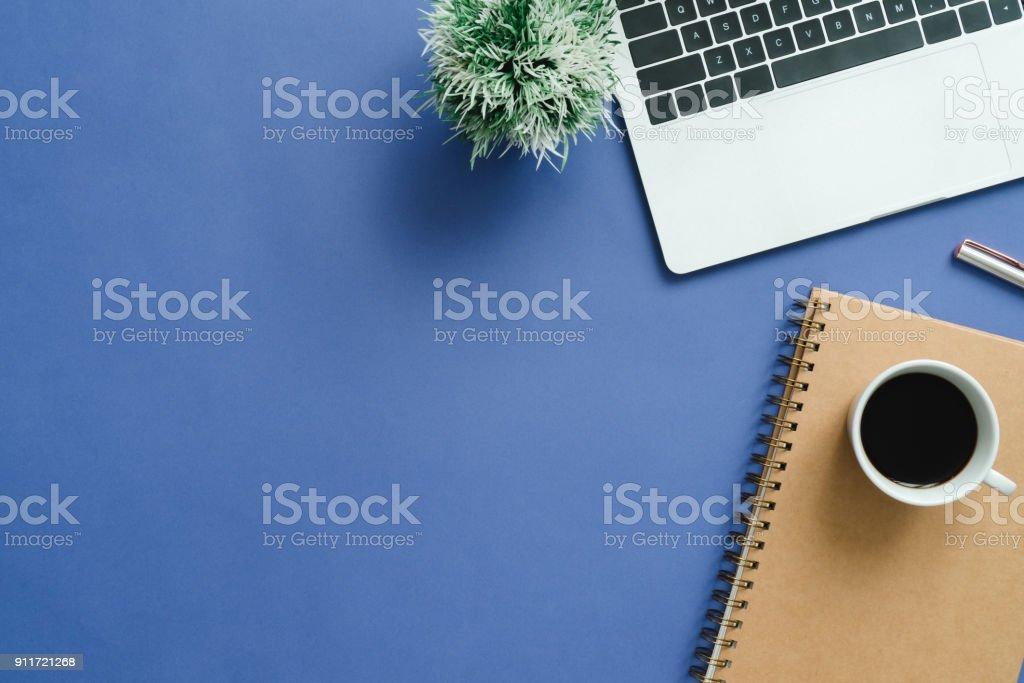Espacio de trabajo mínimo - plano creativo pone foto de escritorio de espacio de trabajo. Escritorio de oficina de la vista superior con ordenador portátil, ordenadores portátiles y taza de café sobre fondo de color azul. Vista con espacio de copia superior, endecha plana fotografía. foto de stock libre de derechos