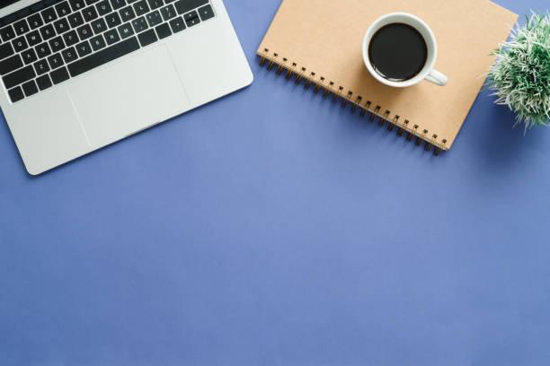 Minimale Arbeitsraum - kreative Wohnung lag Foto des Arbeitsbereichs Schreibtisch. Draufsicht Schreibtisch mit Laptop, Notebooks und Kaffeetasse auf blaue Hintergrundfarbe. Draufsicht mit Textfreiraum, Fotografie flach zu legen. – Foto
