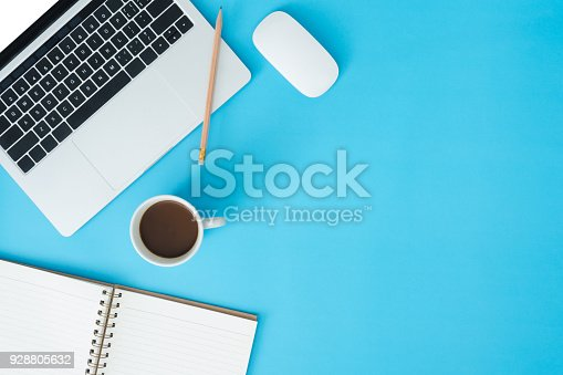 istock Minimal work space - Creative flat lay photo of workspace desk. Top view office desk with laptop, notebooks and coffee cup on blue color background. Top view with copy space, flat lay photography. 928805632