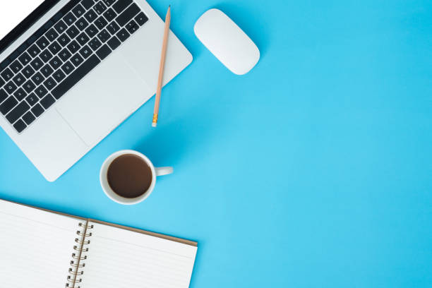 Minimal work space - Creative flat lay photo of workspace desk. Top view office desk with laptop, notebooks and coffee cup on blue color background. Top view with copy space, flat lay photography. stock photo