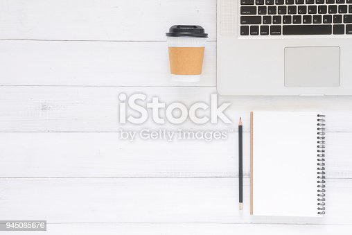 843371502 istock photo Minimal work space - Creative flat lay photo of workspace desk. Top view office desk with laptop, mockup notebooks and coffee cup on wooden background. Top view with copy space, flat lay photography 945065676