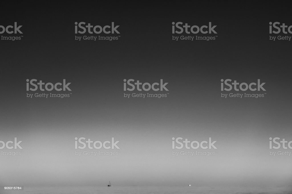 Minimalism, black and white picture of small boat at the horizon,...
