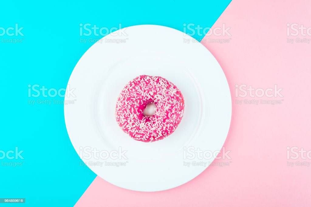 Minimalism, colour contrast on a blue and pink background, donut photo from above in flat style royalty-free stock photo