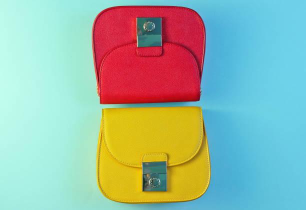 minimalismus modekonzept. rote und gelbe minibeutel mit gradierter grün-blauer holografischer farbe. top view - neontasche stock-fotos und bilder