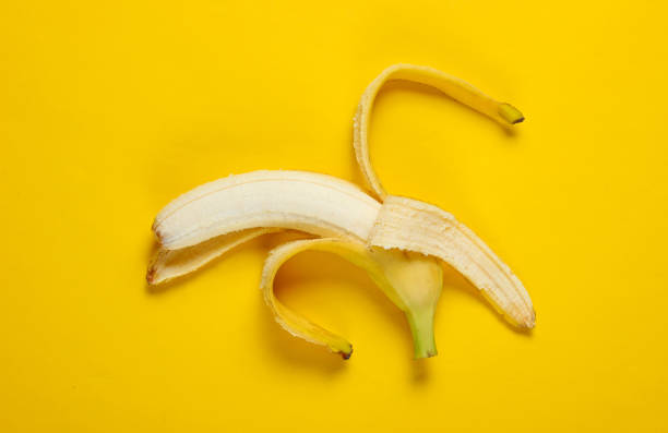 Minimalism fruit concept. Opened ripe banana on a yellow background. Top view Minimalism fruit concept. Opened ripe banana on a yellow background. Top view banana peel stock pictures, royalty-free photos & images