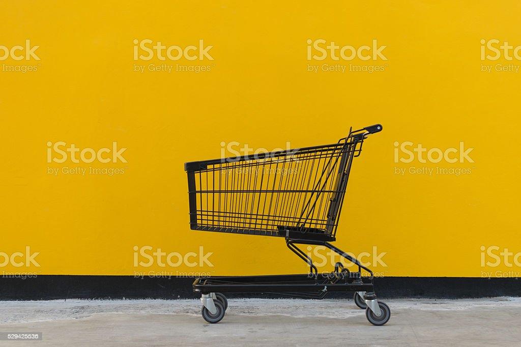Minimalism style, Shopping cart and yellow wall. stock photo