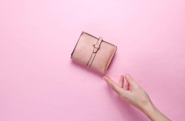 ミニマリズムトレンド。女性の手はピンクのパステル背景にピンクの革の財布を取ります。トップビュー - 財布 ストックフォトと画像