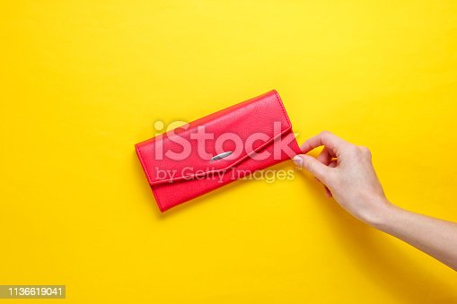 Minimalism trend. Female hand takes red leather wallet on yellow background. Top view
