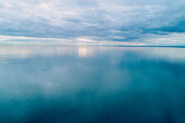 Minimalist aerial seascape. Overcast sky over calm and smooth water surface Minimalist aerial seascape. Overcast sky over calm and smooth water surface horizon over water stock pictures, royalty-free photos & images