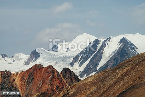 Minimalist beautiful alpine landscape with huge snowy mountain behind vivid pointed red craggy wall. Big glacier under blue sky. Atmospheric colorful highland scenery with giant red orange brown rock.