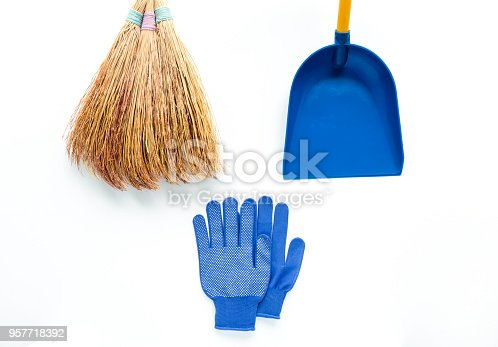 istock Minimalist cleaning composition on white background. Fabric gloves, broom and scoop. Flat lay 957718392