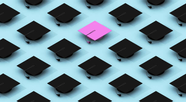 Minimalist composition pattern with black graduation caps and one pink on a blue background stock photo