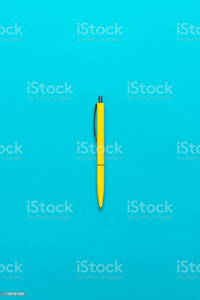 top view of ballpoint pen on the blue background. minimalist flat lay...