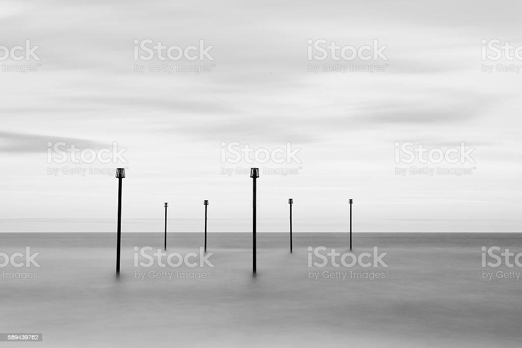 Minimalist landscape image of old sea warning posts stock photo