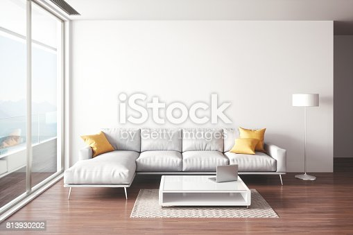 Interior of a modern minimalist living room with sofa, coffee table and floor lamp with beautiful sea view.