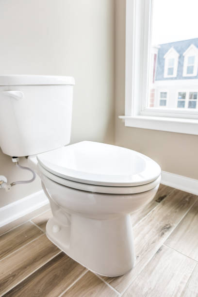 Minimalist modern clean white toilet in restroom with window in model house, home or apartment stock photo