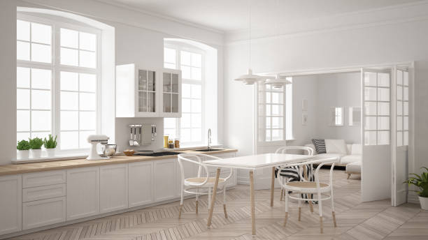 Minimalist scandinavian white kitchen with living room in the background, classic white interior design stock photo