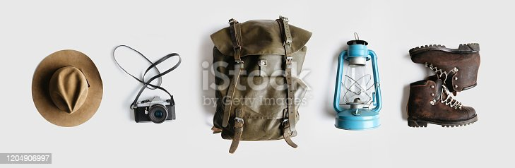 Vintage adventurer essential gear flat lay. Hat, backpack, film camera, gas lamp and boots on white background isolated. Minimal style hiking concept. Wanderlust vibes.