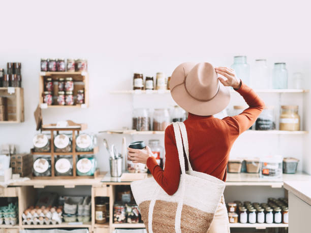 Minimalist vegan style girl with wicker bag and reusable glass coffee cup on background of interior of zero waste shop. stock photo