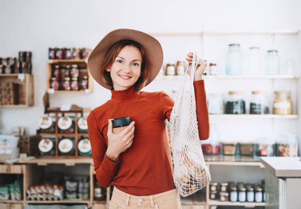 Minimalist vegan style young woman with cotton reusable net mesh bag and reusable glass coffee cup on background of goods of zero waste shop. stock photo