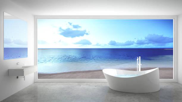 minimalistische weiße und graue badezimmer mit großen panorama-fenster, sommerstrand im hintergrund - badewannenkissen stock-fotos und bilder
