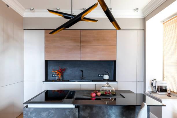 minimalistische graue holzküche mit grifflosen fassaden, beeindruckender lampe, kücheninsel und herbstdekor, intelligentes aufbewahrungssystem. küchenraumorganisation - küche deko blog stock-fotos und bilder