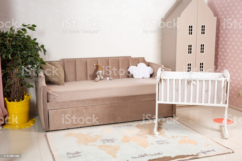 Minimalistic baby's room interior with an elegant child's bed and sofa for mom