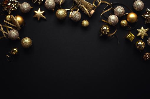 Christmas Flat Lay Background. Black Baubles on Dark Black Background. Minimalistic design. Copy Space. Horizontal.