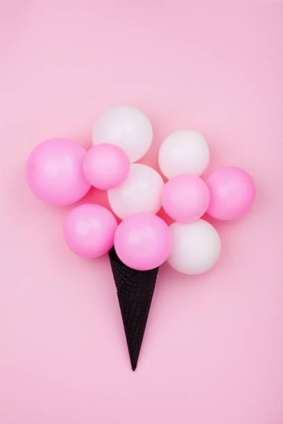 minimalistische komposition für geburtstag mit ballons eis waffelhörnchen rosa pastell hintergrund draufsicht. flach zu legen. - eis ballons stock-fotos und bilder