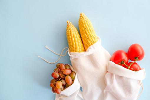 istock Minimalistic compositions with bunch of different fruits and vegetables in recyclable sack. 1030424504