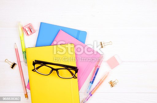 istock Minimalistic flat lay composition with girlie set of school supplies on wooden table. Woman's desktop w/ accessories. 968838362