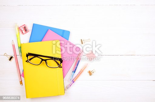istock Minimalistic flat lay composition with girlie set of school supplies on wooden table. Woman's desktop w/ accessories. 968838374