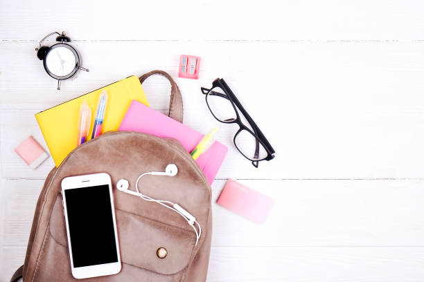 Minimalistic flat lay composition with girlie set of school supplies on wooden table. Woman's desktop w/ accessories. stock photo