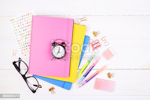 istock Minimalistic flat lay composition with girlie set of school supplies on wooden table. Woman's desktop w/ accessories. 968838474