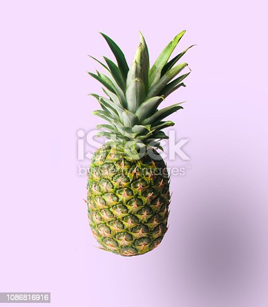 917861766istockphoto Minimalistic fruit concept. Pineapple isolated on pastel background. Photo with a shadow. 1086816916
