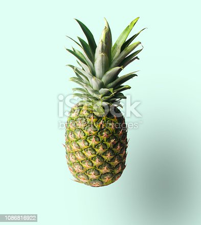917861766istockphoto Minimalistic fruit concept. Pineapple isolated on pastel background. Photo with a shadow. 1086816922