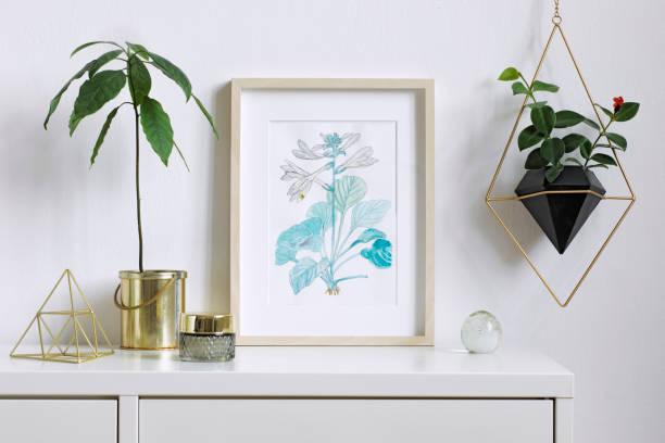 minimalistische nach hause innen floral plakat mock-up mit vertikalen hölzernen bilderrahmen, avocado pflanze, zubehör und hängende pflanze in geometrischen topf auf weiße wand hintergrund. konzept der weißen regal. - desktop foto stock-fotos und bilder
