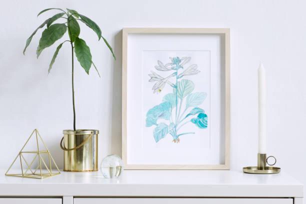 minimaliste maison intérieur floral affiche mock up avec cadre photo en bois vertical, avocat plante, pyramide or et accessoires sur fond de mur blanc. notion de plateau blanc. - camera sculpture photos et images de collection