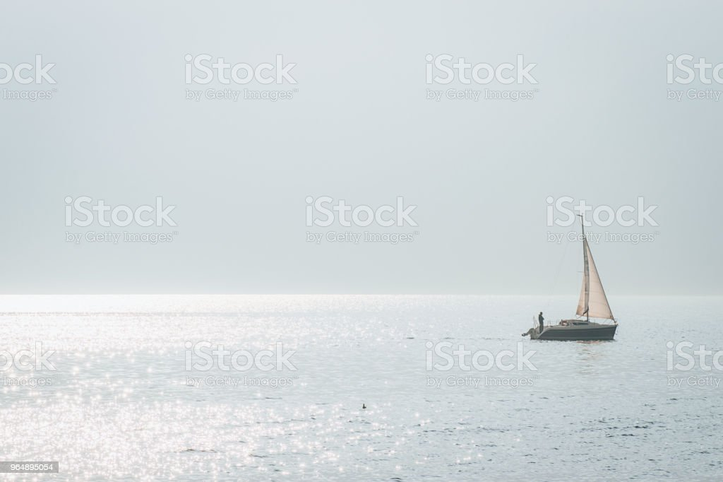 Minimalistic landscape with a sailing boat on the Alpine Lake Iseo royalty-free stock photo
