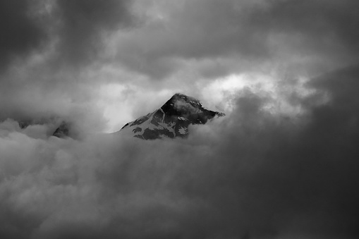 Minimalistic monochrome image of mountain peak shrouded in clouds
