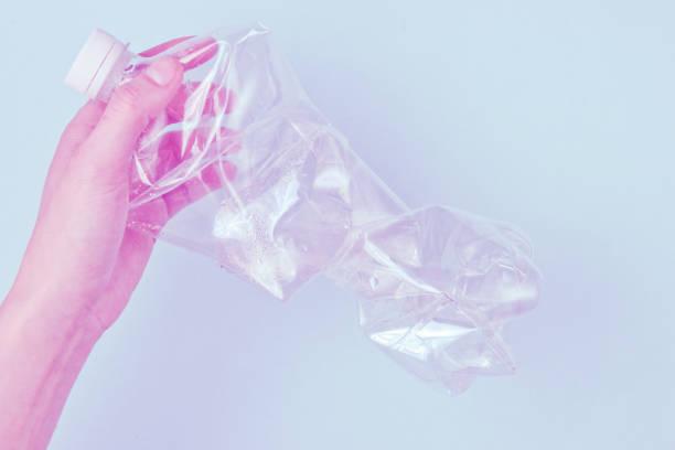 conceito minimalista de ecologia da poluição. mãos femininas torcem garrafa de plástico rumpled. foto vestida. vista superior - squeeze bottle - fotografias e filmes do acervo