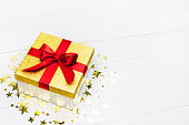 istock Minimalistic present, golden stars confetti above on white table. Square gift box with red ribbon wallpaper with space 1281878580